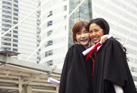 Beautiful two Asia girl students are happy after graduation. Stok Fotoğraf - 124612141