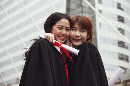 Beautiful two Asia girl students are happy after graduation. Stok Fotoğraf - 124612144