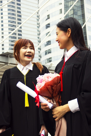 Beautiful two Asia girl students are happy after graduation.
