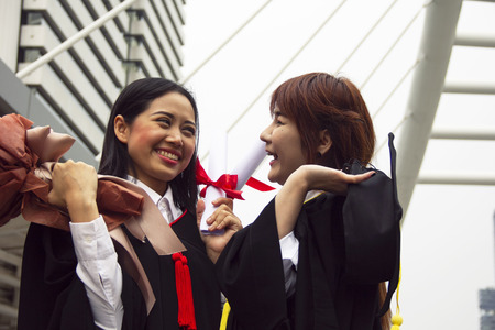 Beautiful two Asia girl students are happy after graduation. Stok Fotoğraf - 124613619