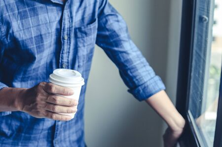 Business man holding coffee cup and standing thinking creative work at homework. Stok Fotoğraf