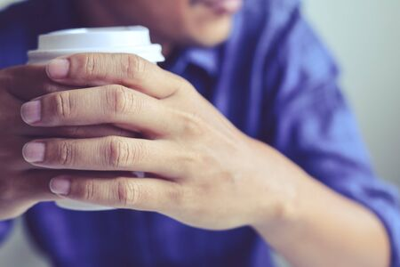 Close-up business man hand holding coffee cup and thinking creative work in home office. Stok Fotoğraf