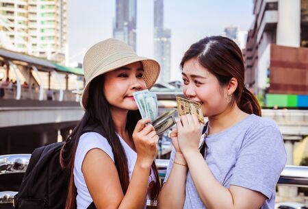 Beautiful two woman happy holding money for traveling in the city.