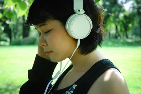 Beautiful sport woman smile portrait and listening music in public park. Stok Fotoğraf