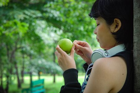 Beautiful Asia sport woman holding green apples and walking in public park.