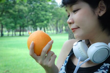 Beautiful woman sport holding orange fruits for healthy food concept.