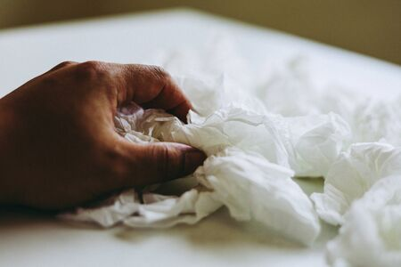 Close-up hand holding white paper tissue background.