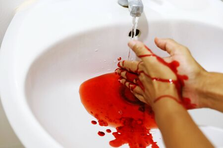 Close up washing the blood out of the hands in the bathroom. Standard-Bild - 135374136