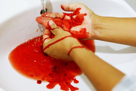 Close up washing the blood out of the hands in the bathroom. Standard-Bild