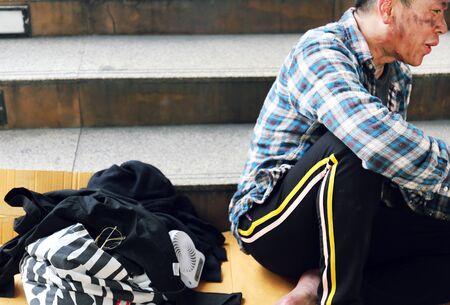 Senior homeless man sitting and ralaxation lifestyle on walking street.