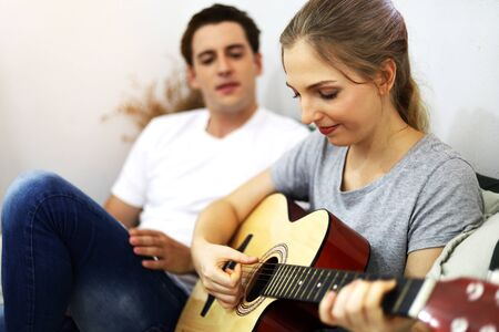 Young couple lover playing acoustic guitar on bedroom at home. Archivio Fotografico