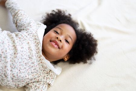 Beautiful African american girl kid smile portrait in bedroom at home. Stock Photo