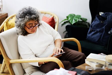 Beautiful senior woman sitting relaxation and reading online book on mobile phone device in home.