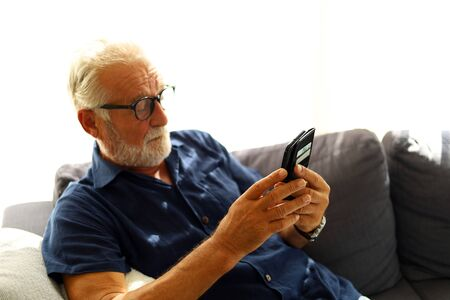 Elderly senior man sitting alone and playing mobile phone at home. Фото со стока - 146386648
