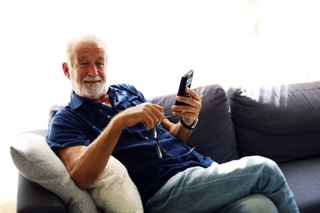 Elderly senior man sitting alone and playing mobile phone at home. Stock Photo