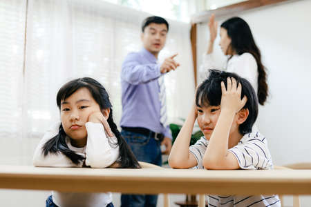 Unhappy family problems concept, father and mother quarreling in the house so causing children to feel bad.