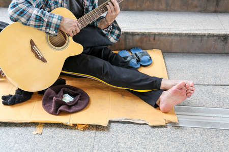 Senior homeless man sitting and playing acoustic guitar.