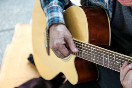 Senoir homeless man sitting and playing acoustic guitar.
