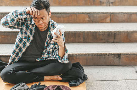 Asia Senior homeless man on walkway street in the city.