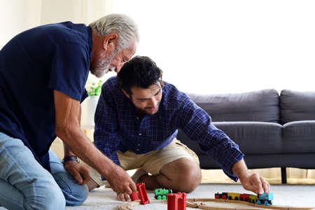 Happiness father and son having fun with childhood toys at home.