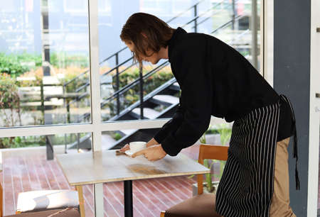Coffee shop owner man cleaning on table at cafe. 免版税图像