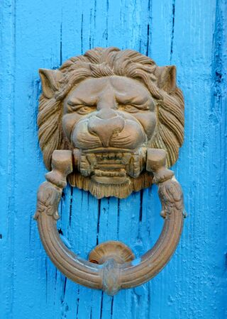 Door knocker with a lion on it on a blue wooden door Stock Photo