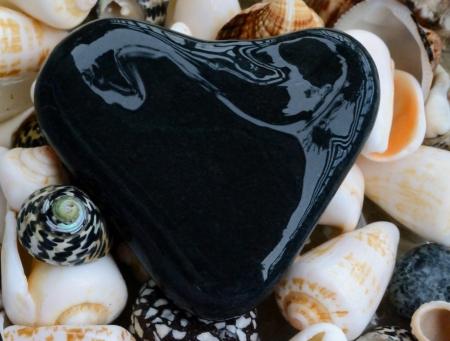 A stone shaped as a heart and sea shells Stock Photo