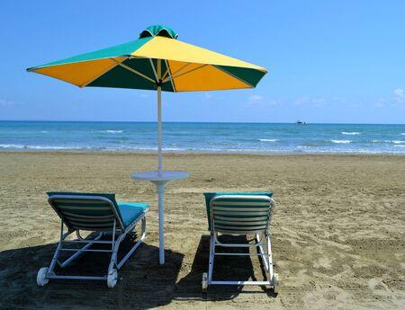 Sunbeds, umbrella and sea