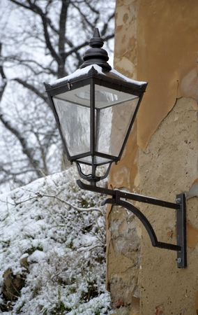 Oude straatlantaarn met sneeuw op muur