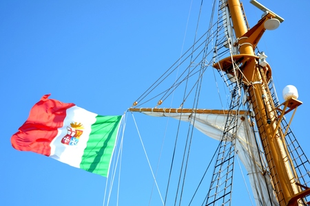 Details of outdoor exterior of an Italian ship with flag and blue sky