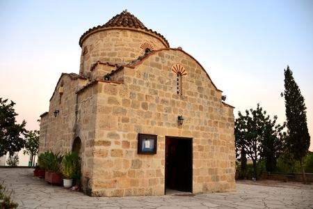 Outdoor exterior of Agios Georgios Makri chapel with cloudy blue sky and trees