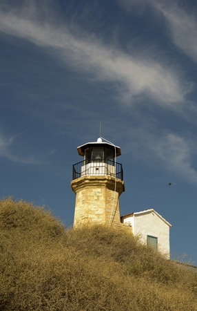 Outdoor architecture of an old lighthouse in Cyprus and cloudy blue sky