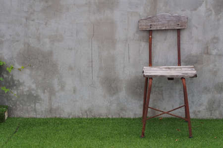 relent: An old wooden-steel chair is put on field in front of concrete wall