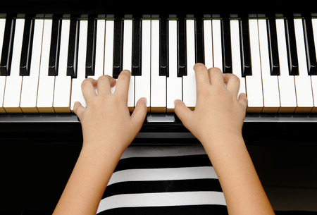 keyboard instrument: hands of kid playing piano Stock Photo