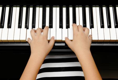 teclado de piano: manos de ni�o tocando el piano