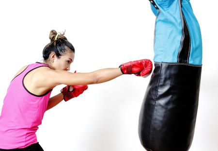 sandbag: attractive young woman making a punch on the blue sandbag Stock Photo