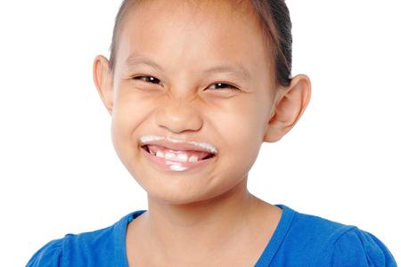 milk mustache: Close up fun portrait of cute asian girl showing white milk mustache isolated