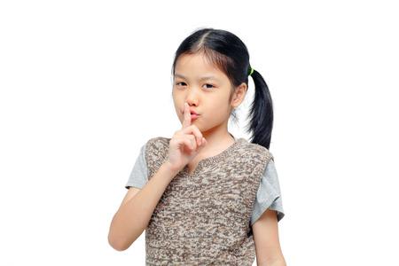 guardar silencio: muchacha asiática joven manteniendo el dedo en sus labios