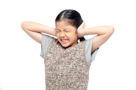 Aziatisch meisje die haar oren met de handen.