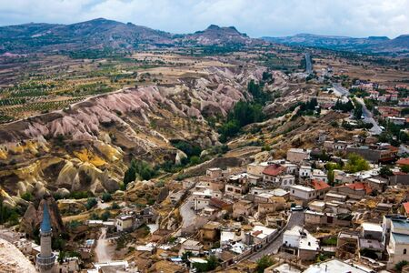 Hilly landscape showing  the impressive volcanic valley with small town near by and mosk. Birds eye view.