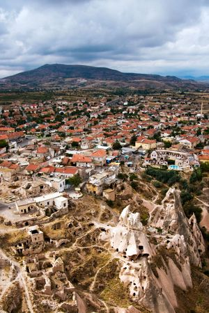 Hilly landscape with distant horizon,small town tiled roofs and ruins foreground. Birds eye view. Stock Photo