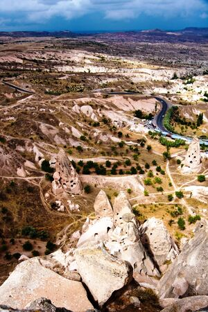 Hilly landscape with distant horizon, rocky houses ruins and winding road