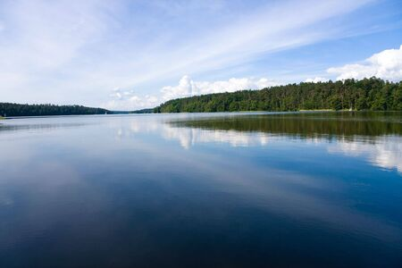 Lake in the forest. View at the wide and calm lake surface in the forest, at sunny day. Blue cloudy sky