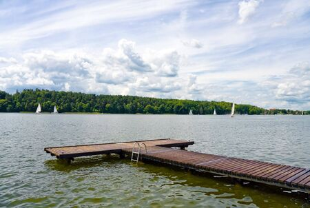 Wooden Pier on lake,sailing boats and forest. Blue cloudy sky.