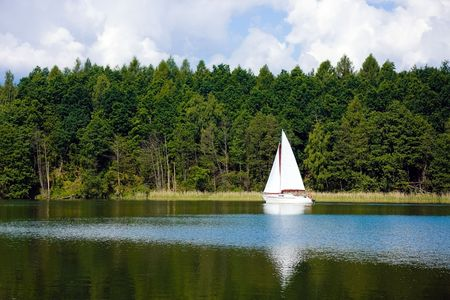 Sailing boat, green forest and lake background.