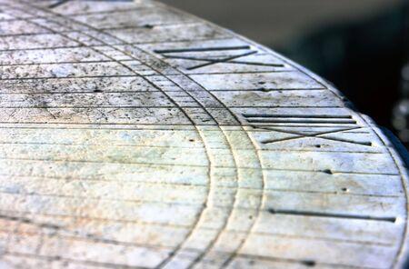 Ancient granite sundial closeup. Engraved 12th hour digit