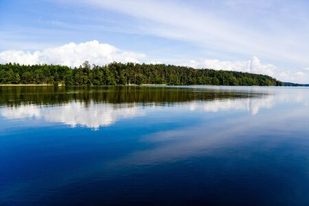 Wide, calm lake surface in the forest, sunny day. Blue cloudy sky. Stock Photo