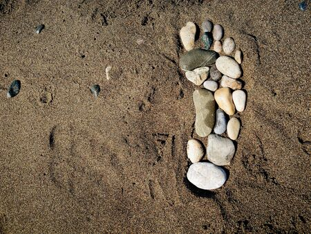 Stone foot in the sand photo