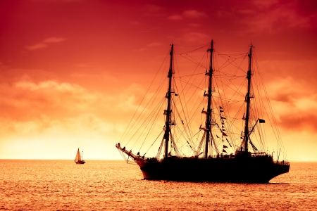 Sailing tall ship and  red clouds Stock Photo