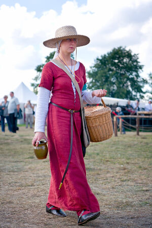 reenactor: Woman returns from the medieval market Editorial